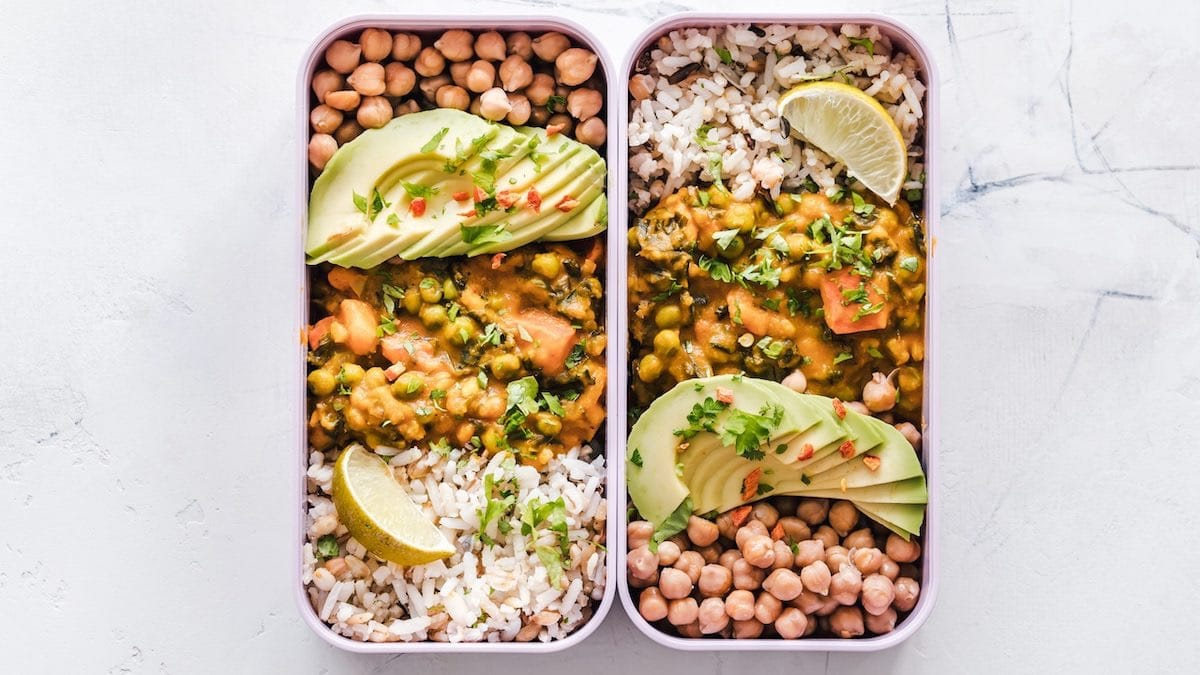 Two Trays of Food: Rice, Peas, Garbanzo Beans, Garnished with Sliced Avocado & Lemon Wedge